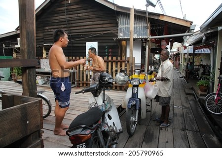 GEORGETOWN, MALAYSIA - MAY 29: A traditional food vendor and customers on the Clan Jetties at Georgetown, Malaysia on the 29th May, 2014.