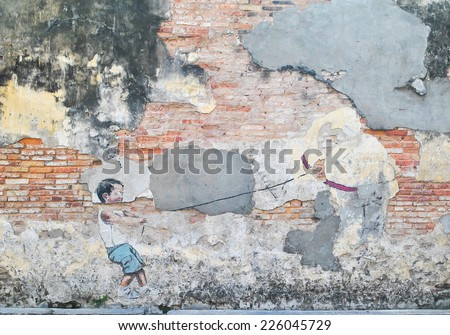 """Georgetown, Penang, Malaysia - July 14, 2013: """"Little Boy with Pet Dinosaur"""" street art piece in George Town, Penang, Malaysia. - stock photo"""