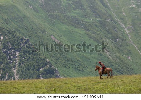 Georgia - circa July 2016: a man in traditional clothing riding a horse in the mountains