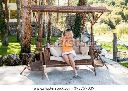 Georgia. The hotel in the mountains young woman sits resting in a wicker chair swing - stock photo