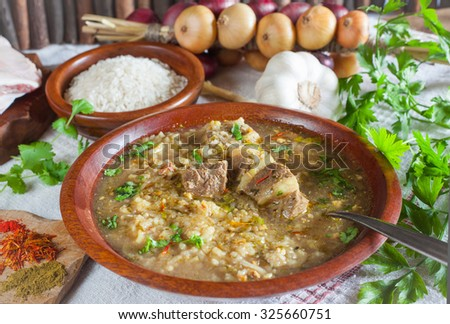 Georgian beef-walnut soup Kharcho with rice, onion, garlic, parsley, coriander and marigold in wooden cup with metal spoon on the linen table Cloth with wooden Background horizontal - stock photo