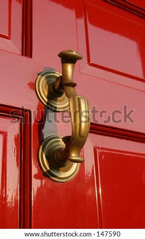 Georgian Door Knocker on burgundy paneled wooden door. - stock photo
