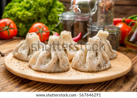 Georgian dumplings Khinkali with meat, greens and tomato spicy sauce Satsebeli on white plate