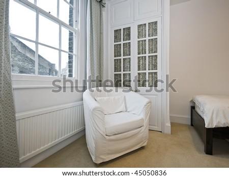 georgian house bedroom detail with armchair and double door wardrobe - stock photo