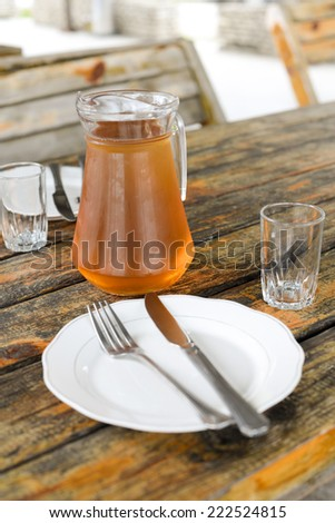 Georgian Wine Rqatsiteli served in a glass jar, two small wine glasses, cutlery, wooden surface, table - stock photo