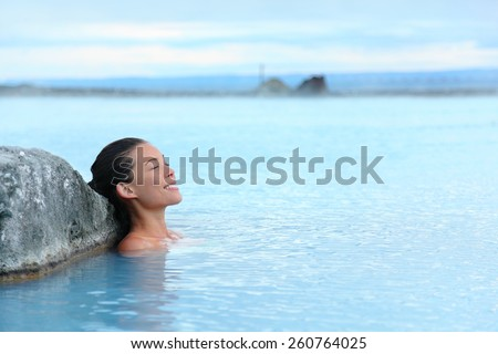 Geothermal spa. Woman relaxing in hot spring pool on Iceland. Girl enjoying bathing in a blue water lagoon Icelandic tourist attraction. - stock photo
