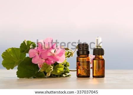 Geranium essential oils in bottles - stock photo