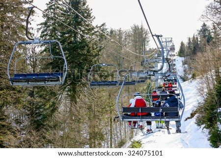 GERARDMER, FRANCE - FEB 19 - Skier using the ski lift during the annual winter school holiday on Feb 19, 2015 in Gerardmer, France - stock photo