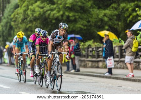 GERARDMER, FRANCE - JUL 12: A group of four cyclists riding during a rainy day in the stage 8 of Le Tour de France on July 12, 2014 in Gerardmer.