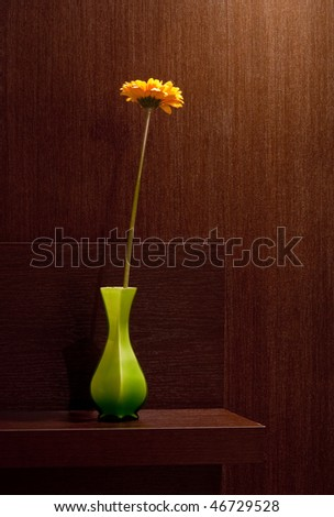 gerbera in vase at brown home background.