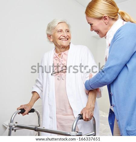 Geriatric nurse helping senior citizen woman with walker - stock photo