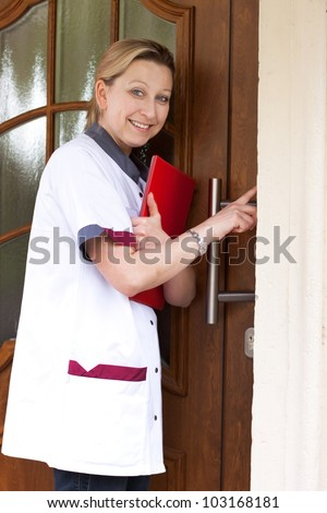 Geriatric nurse makes a house call and rings the door - stock photo