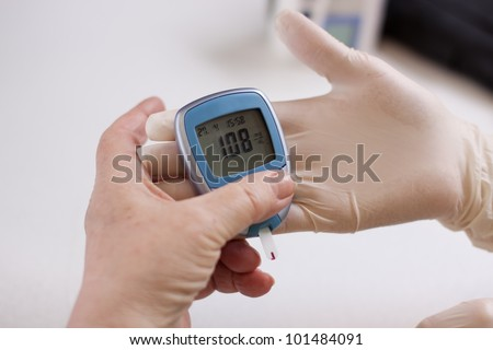 Geriatric nurse measures with glucose meter - stock photo