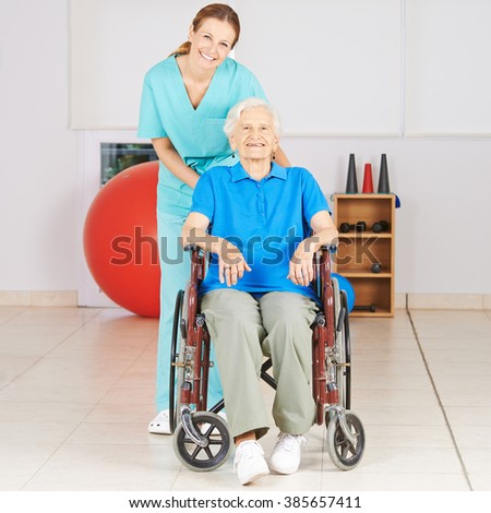 Geriatric nurse with old woman in wheelchair at physiotherapy - stock photo
