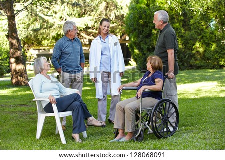 Geriatric nurse with senior group in garden of a retirement home - stock photo