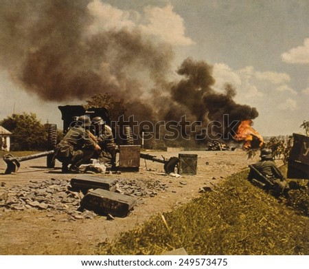 German anti-tank gun team on road with a flaming tank in background. Ca. 1939-45. WW2 in Russia. - stock photo