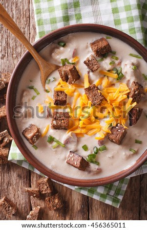 German beer soup with cheese and bacon close up in a bowl on the table. Vertical view from above - stock photo