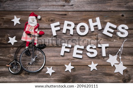 German christmas greeting card with german text merry christmas. Xmas decoration with a red santa claus on a bicycle. - stock photo