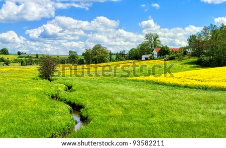 German countryside landscape with creek and yellow canola field - stock photo