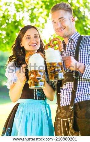 German couple in Tracht drinking beer in the shadow of trees - stock photo