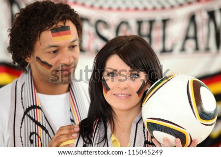 German couple supporting their soccer team - stock photo