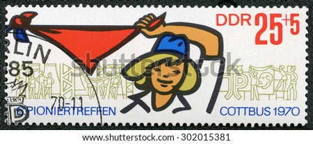 GERMAN DEMOCRATIC REPUBLIC - CIRCA 1970: A stamp printed in GDR Germany shows Pioneer Girl Holding and Waving Kerchief and Pioneer Activities, circa 1970