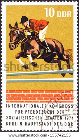 "GERMAN DEMOCRATIC REPUBLIC - CIRCA 1974: A stamp printed in Germany from the ""International Horse breeders' Congress, Berlin"" issue shows Show Jumping, circa 1974."
