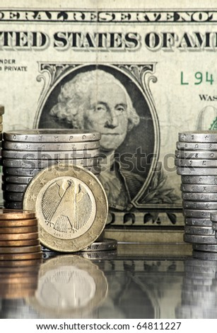 german euro coin with us dollar banknote in background - stock photo