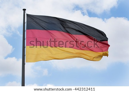 german flag against cloudy blue sky