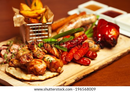 German food concept. Set of fried meat and small meat sausages served with scallion and dried herbs on wooden cutting board with fried potato pieces and set of different sauces. Close up - stock photo