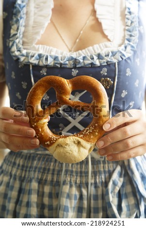 German girl in traditional dress with pretzel - stock photo