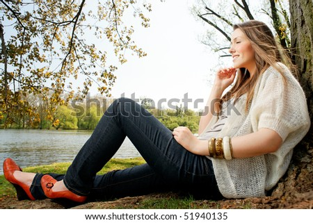 German girl sitting in the park. - stock photo