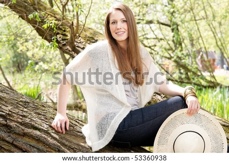 German girl sitting on a trunk in the park.