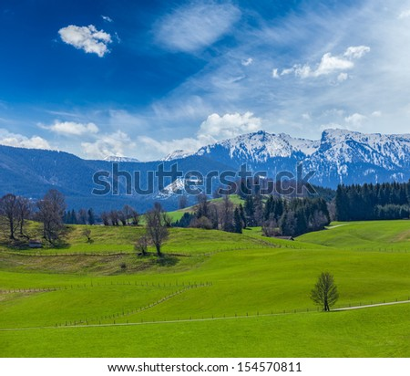German idyllic pastoral countryside in spring with Alps in background. Bavaria, Germany