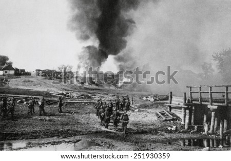 German infantry advancing on a burning village in the Soviet Union (Russia). Summer of 1941, during World War 2. - stock photo
