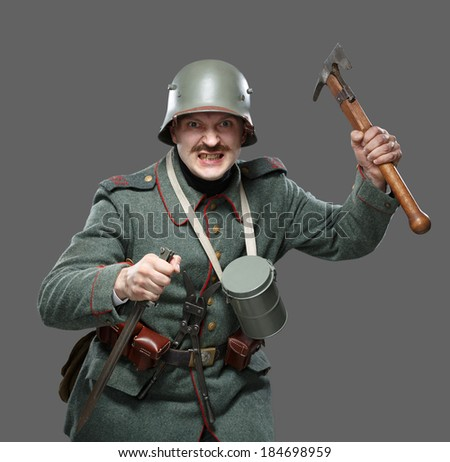 German infantryman during the first world war. Soldiers attacked with an ax and a bayonet. Isolated on gray. - stock photo