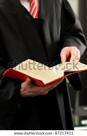 German Lawyer with civil law code in a court room, close-up, only torso to be seen - stock photo