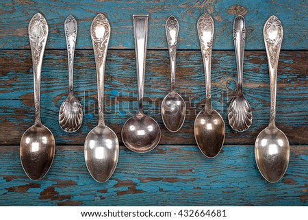 German silver spoon and fork on a wooden background. Kitchen utensils. - stock photo
