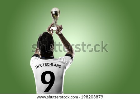 German soccer player, celebrating the championship with a trophy in his hand. On a green background. - stock photo