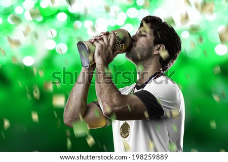 German soccer player, celebrating the championship with a trophy in his hand. On a green lights  background. - stock photo