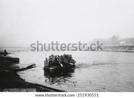 German soldiers crossing the Dnieper River in a small boat. By the end of August 1941, Southern Nazi Armies has crossed the river and established strategic beachhead from which they advanced on Kiev. - stock photo