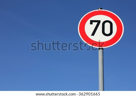 german speed limit sign 70 km/h against blue sky