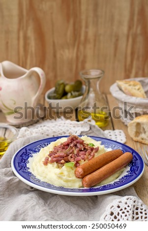 German style mashed potatoes with apples served with sausages and bacon. Selective focus - stock photo