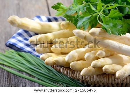 German white asparagus in a basket and decorated with parsley - stock photo