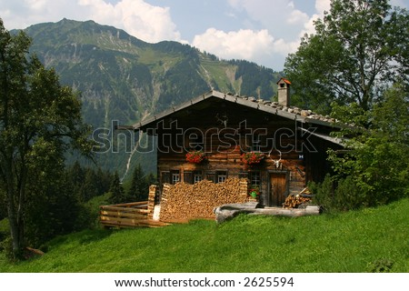 "German wooden house within the mountains. Green grass. ""Almhuette"" - stock photo"
