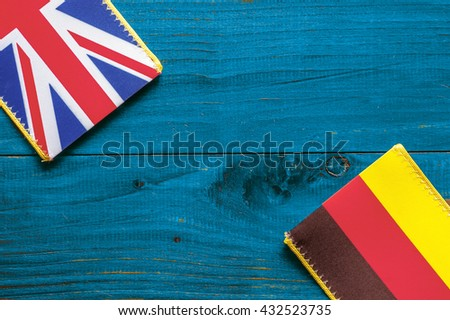 Germany and British flag on the blue wooden background - stock photo