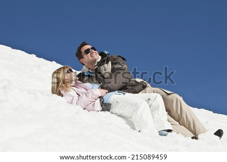 Germany, Bavaria, Couple in winter clothes lying in the snow - stock photo