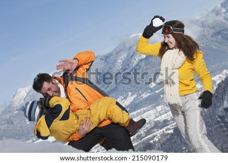 Germany, Bavaria, Family having snowball fight - stock photo