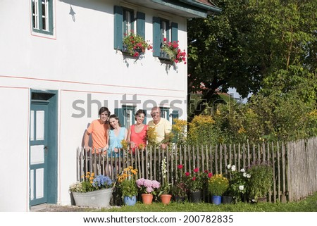 Germany, Bavaria, Four people standing by the fence in garden - stock photo