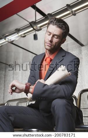 Germany, Bavaria, Munich, business man at subway station looking at watch - stock photo